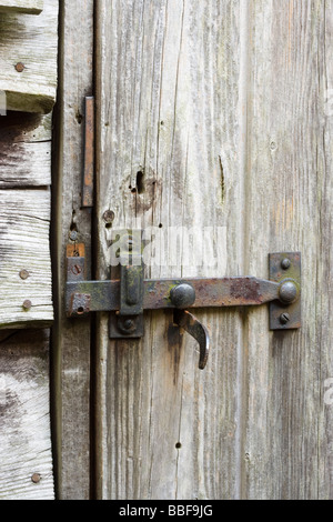 Latch and lock on old shed door. - Stock Photo