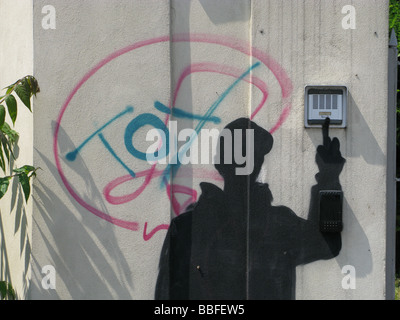 dark person graffiti ringing doorbell on property in street road - Stock Photo