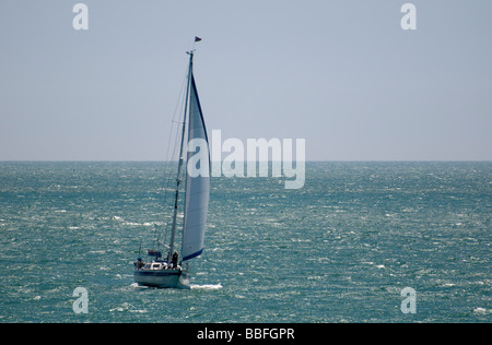 A sailing yacht with its jib raised - Stock Photo