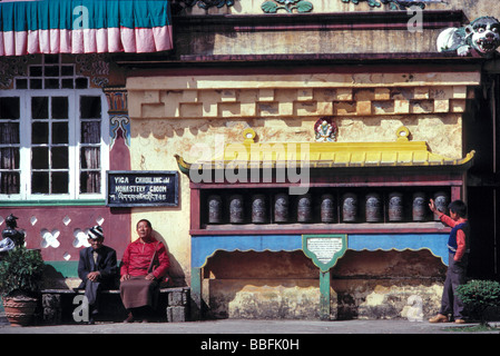 Men sit with their faces tilted to the sun outside Ghoom Monastery in Darjeeling India - Stock Photo