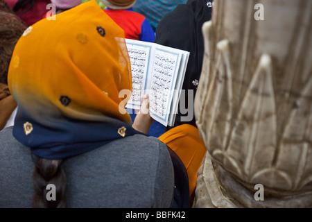 Muslim Woman Reading from the Quran at Hazrat Nizamuddin Shrine in Delhi India - Stock Photo