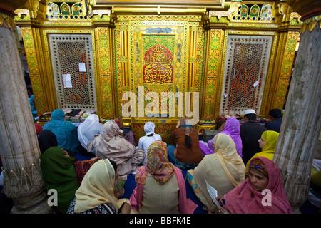 Muslim Women Worshipping at Hazrat Nizamuddin Shrine in Delhi India - Stock Photo
