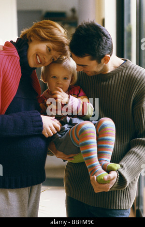 Parents holding little girl, smiling - Stock Photo