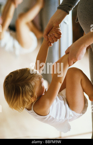 Little girl holding mother's hands, turning flip against her stomach - Stock Photo