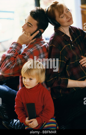Family sitting back to back, father using cell phone, mother listening to headphones, daughter watching TV - Stock Photo
