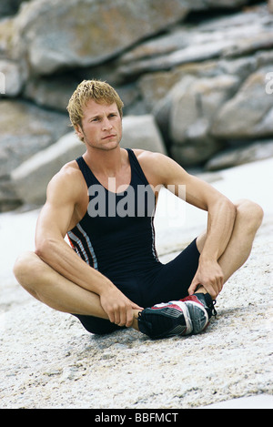 Young man sitting with soles of feet together doing stretches outdoors - Stock Photo
