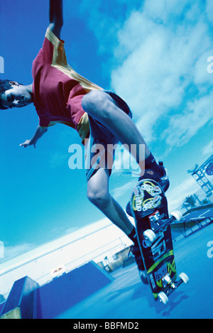 Skateboarder doing trick, low angle view - Stock Photo