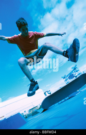 Skateboarder doing trick in midair, low angle view - Stock Photo