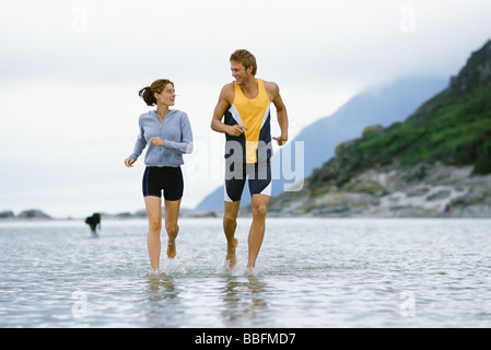 Young couple running together through shallow  water near shore - Stock Photo