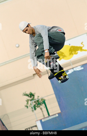 Skateboarder doing midair trick at skatepark - Stock Photo