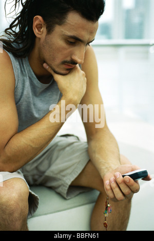 Man sitting with hand under chin, looking at cell phone - Stock Photo