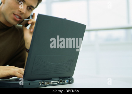Man phoning, using laptop computer, low angle view - Stock Photo
