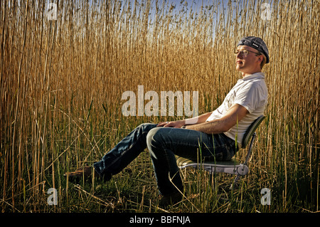 Man sitting on an office chair in dry reeds - Stock Photo