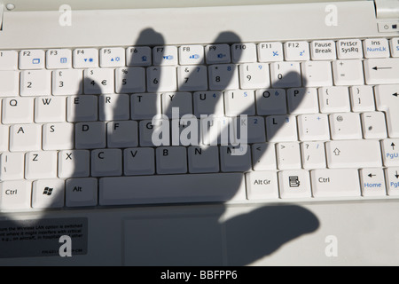 Shadow of palm of hand over computer keyboard. - Stock Photo