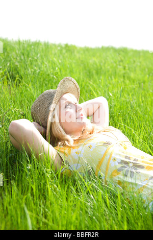 Portrait of a smiling blond girl wearing a sun hat while lying on a meadow - Stock Photo