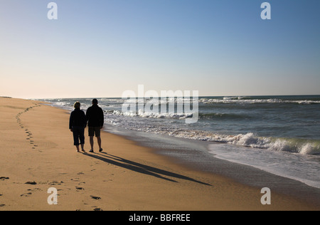 Couple strolling along the beach at sunrise. - Stock Photo