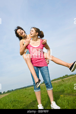 Girl carrying her friend piggy-back over a meadow - Stock Photo