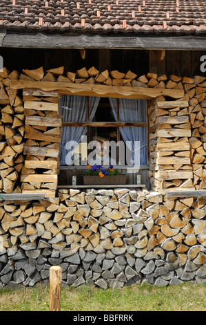 Firewood stacked around a barn with a manikin in the window, Mittenwald, Bavaria, Germany - Stock Photo