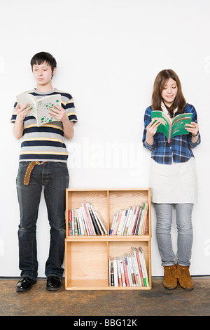 Young man and woman reading books - Stock Photo