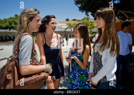 White and Asian Southern California high school girls enjoy each others company during lunchtime on campus - Stock Photo