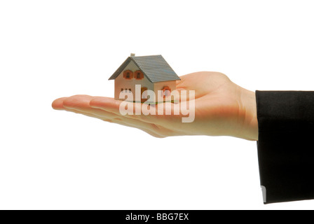 Model home standing on a female hand, symbolic of real estate - Stock Photo