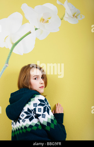 Young girl standing in front of a wallpaper with flower Stock Photo