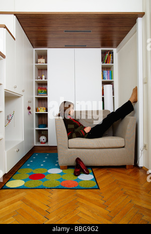 Young girl sitting on the armchair in her room - Stock Photo