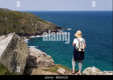 Female walker looking over Brea Cove to Carn Naun Point on the SWC footpath - Stock Photo