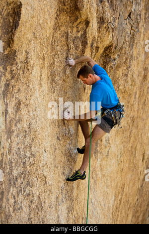 Climber ascends a steep rock overhang. - Stock Photo