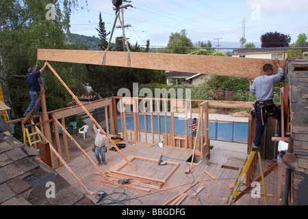 Carpenters placing a heavy ridge beam into brackets as it is lowered by a crane - Stock Photo