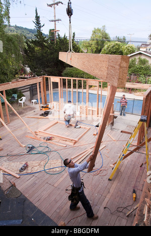 Giant ridge beam being held by a crane and swiveled into position by a carpenter at a residential remodel construction - Stock Photo