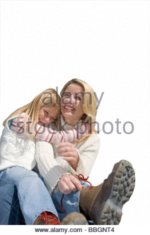 Girl embracing mother beside car, woman tying shoelace, smiling, portrait, cut out - Stock Photo