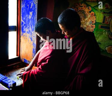Two young Bhutanese Monks playing marbles - Punakha Dzong, Bhutan - Stock Photo