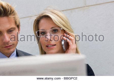 Businesswoman talking on cell phone standing next to businessman, Stuttgart, Baden-Wurttemberg, Germany - Stock Photo