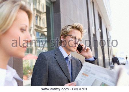Businessman talking on cell phone standing next to businesswoman, Stuttgart, Baden-Wurttemberg, Germany - Stock Photo