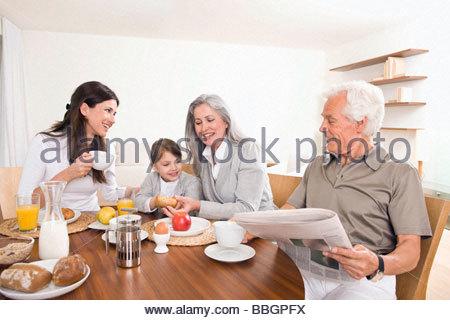 Multi-generation family having breakfast together - Stock Photo