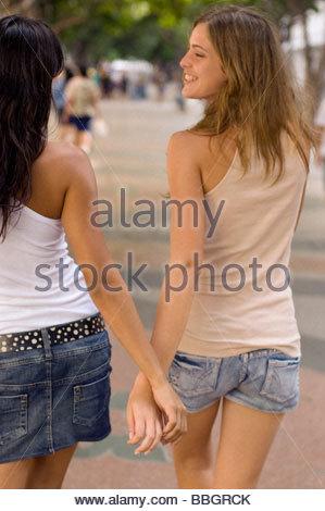 Two young woman walking on road, rear view, Havana, Cuba - Stock Photo