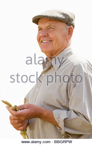 senior man in flat cap holding corn, cut out - Stock Photo