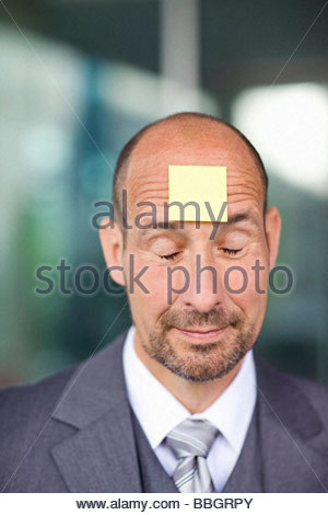 Portrait mature man with note paper stuck on forehead - Stock Photo