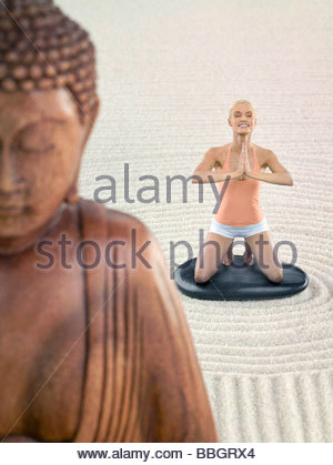 Portrait young adult woman meditating Zen garden, digital composite - Stock Photo