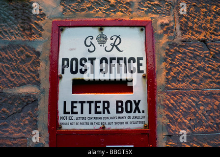 Old post office letter box mounted in a wall in Luss, Loch Lomond - Stock Photo