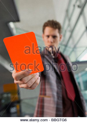 Man suit holding penalty red card - Stock Photo