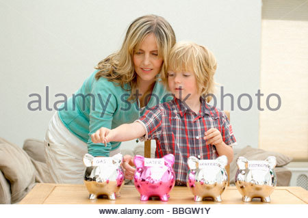 Mother and son putting coin piggy bank, Den Haag, Netherlands - Stock Photo