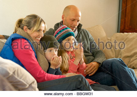 Family winter clothes keeping warm together on sofa - Stock Photo