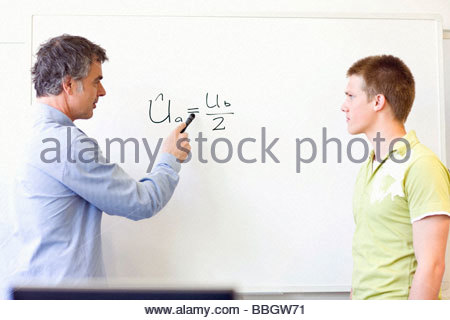 Teacher and student at board discussing an equation - Stock Photo