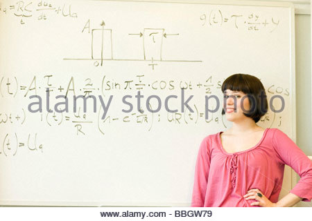 Smiling young woman posing before equation written on board - Stock Photo
