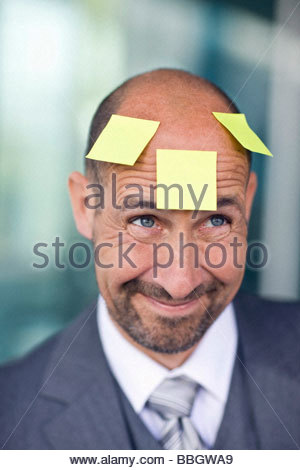 Portrait mature man with three note papers stuck on forehead - Stock Photo