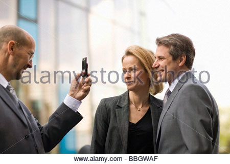 Businessman taking photo with camera phone two other colleagues Munich, Bavaria, Germany - Stock Photo
