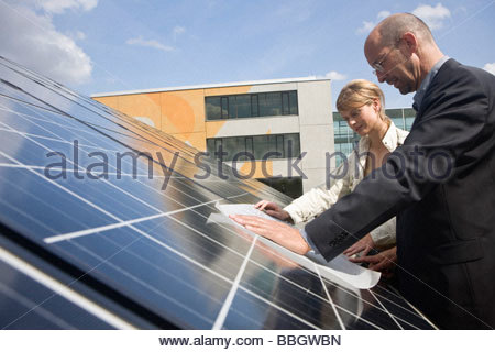 Two mature adults reading plans laid on solar panels Munich, Bavaria, Germany - Stock Photo