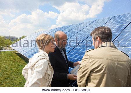 Three mature adults reading plans laid on solar panels Munich, Bavaria, Germany - Stock Photo